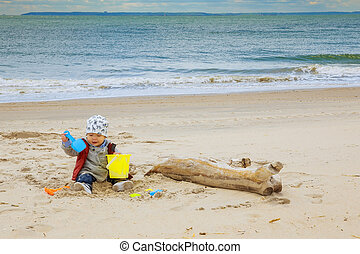 Cute baby boy playing with beach toys