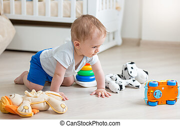 Cute baby boy playing with colorful toys on floor at living room