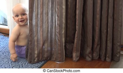 Cute baby boy playing with curtains