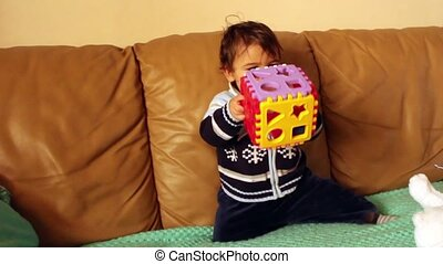 Cute baby boy playing with learning cube