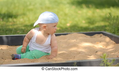 Cute baby boy playing with sand in a sandbox. Summer park and green grass in the background
