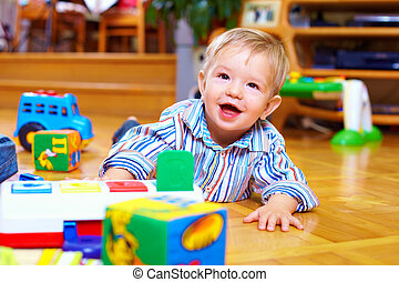 cute baby boy playing with toys in living room