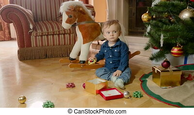 Cute baby boy playing with toys on floor under Christmas tree