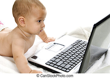 cute baby boy showing curiosity about laptop with white...