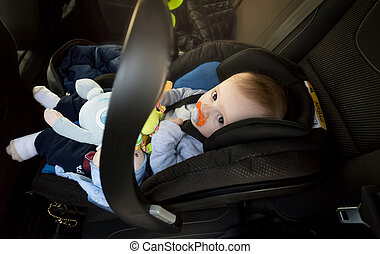 Cute baby boy sitting in baby safety seat at car
