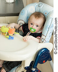 Cute baby boy sitting in child chair with table