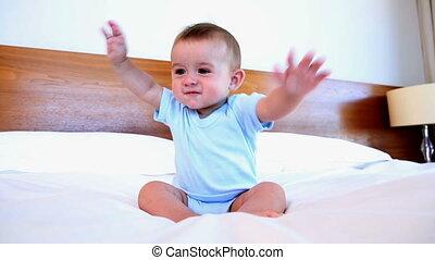 Cute baby boy sitting on bed