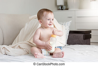 Cute baby boy sitting on bed with milk bottle