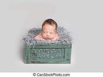 Cute baby boy sleeping in wooden box
