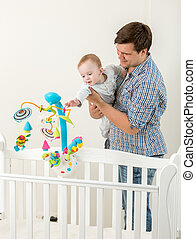 Cute baby boy standing in cot and playing with his father