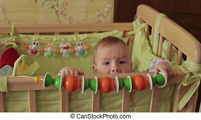 Cute baby boy standing in crib