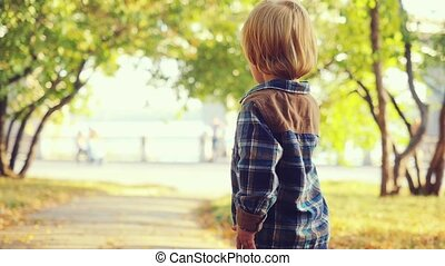 Cute baby boy walks in the park in slowmotion on suny autumn day.