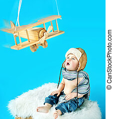 Cute baby boy with an vintage toy plane