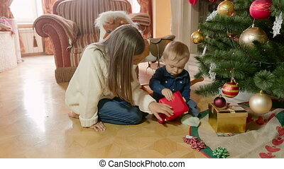 Cute baby boy with elder sister sitting on floor under Christmas tree and opening boxes with gifts