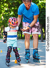 Cute baby boy with inline skating instructor in the park learining to skate.
