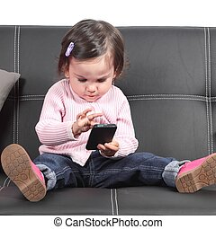 Cute baby browsing in a smartphone sitting on a black couch...