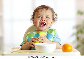 Cute baby child eats healthy food. Portrait of happy kid boy with bib in high chair.