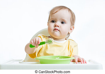 baby child sitting in chair with a spoon