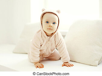 Cute baby crawls in white room at home