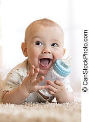 Cute baby drinking water from bottle