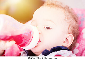 Cute baby drinking water from bottle sitting on chair