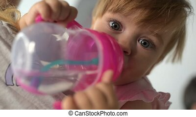 Cute baby drinking water in hands of caring mother