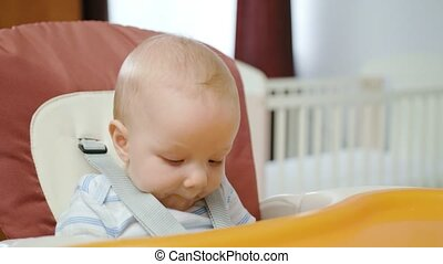 Cute Baby Eating in the Chair at Home