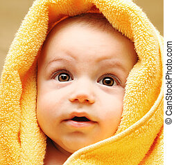 Cute baby face wrapped in towel, hygiene and health care...