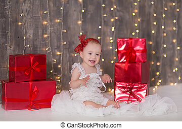 Cute baby girl 1-2 year old sitting on floor with pink balloons in room over white. Isolated. Birthday party. Celebration. Happy birthday baby, Little girl with group ball. Play room.