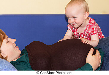 Cute baby girl caressing her pregnant Mother