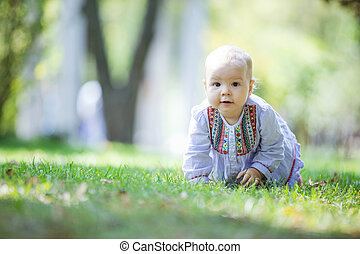 Cute baby girl crawling on lawn in park