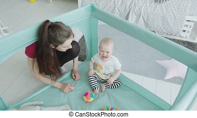 Cute baby girl crying sitting in playpen at home