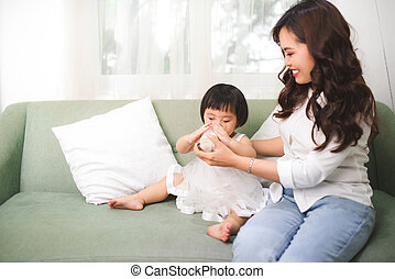 Cute baby girl drinking milk at home with her mom.