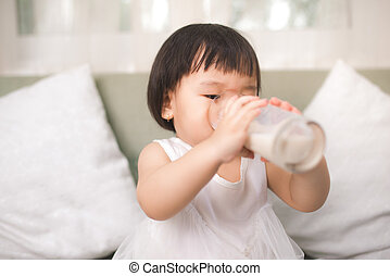 Cute baby girl drinking milk with milk mustache at home