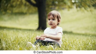 Cute baby girl exploring a park in late spring. Real life,...