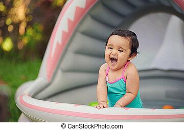 Cute baby girl having fun in inflatable pool