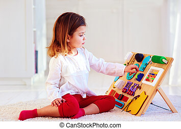 cute baby girl having fun playing with colorful wooden busy board