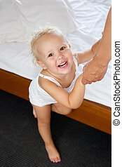 Cute baby girl holding adult hands