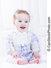 Cute baby girl in a plaid purple dress sitting in a white nursery