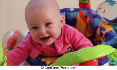 Cute baby girl in bouncer seat