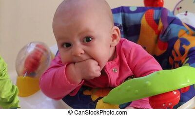 Cute baby girl in bouncer seat two