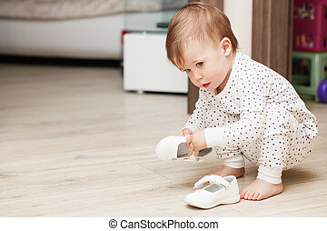Cute baby girl in pajamas squatting on floor tries to put on...