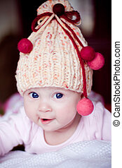 cute baby girl in yellow hat with colourfu bobbles