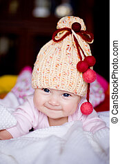 cute baby girl in yellow hat with colourful bobbles