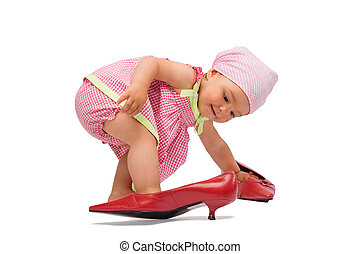 Funny adorable baby girl lady try on a big red women shoes, isolated on white background.