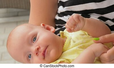 Cute baby girl lying in mothers hands - Slow motion close-up...
