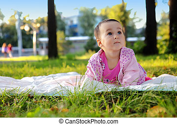 Cute baby girl lying on the grass in the park
