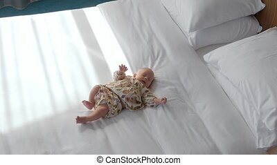 Cute baby girl on white bed linen - Lovely baby girl of 3...