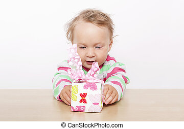 Cute baby girl opening present.
