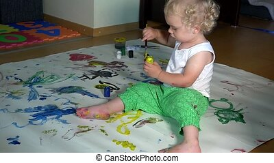 Cute baby girl painting on white paper on the floor at home.